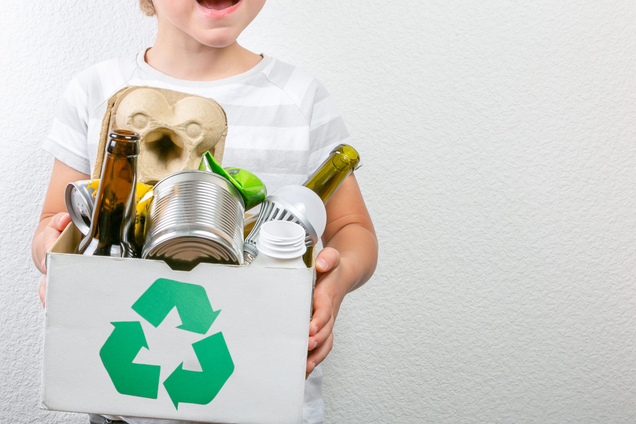 pojke håller i låda med återvinningsbara saker